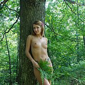 Bewitching lengthy hair girlfriend stripping and posing in the forest.